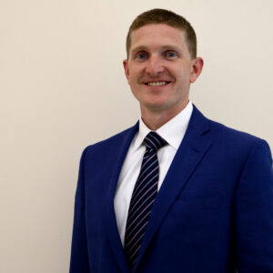 A headshot of Colin Dugan